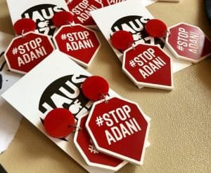 Several pairs of earrings featuring #StopAdani in the shape of a pentagon with a triangle at the bottom
