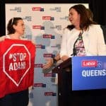 Protestor holding Stop Adani sign on stage with Queensland Premier Annastacia Palaszczuk.