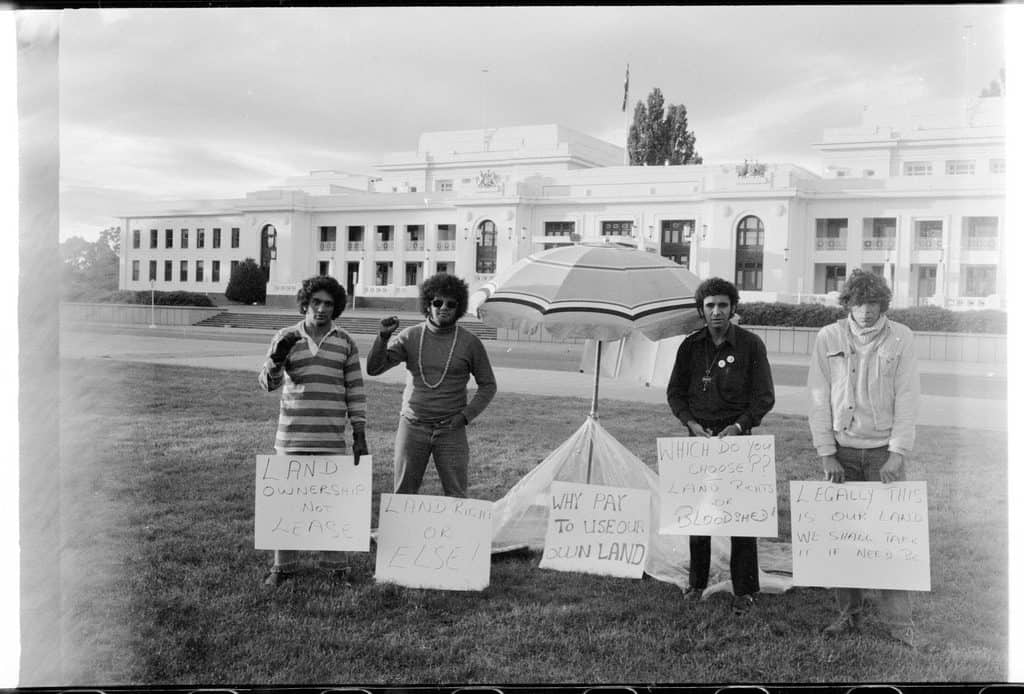 Black and white photograph of four protestors standing in front of Old Parliament House. Placards read 'Land Ownership Not Lease', 'Land Rights or Else!', 'Why Pay to Use Our Own Land', 'Which Do You Choose: Land Rights or Bloodshed?'. 'Legally This is Our Land. We Shall Take It If Need Be'.