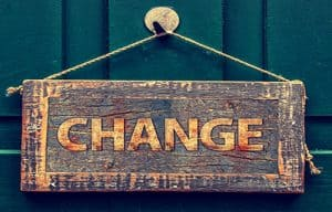 wooden sign saying change hanging on green door