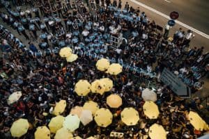 Pro-democracy protesters hold umbrellas in front of police cordon line outside of the Hong Kong Government Complex.