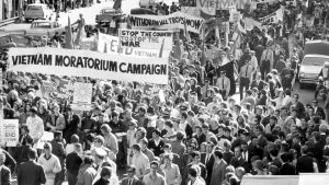 Black and white photograph of a large crowd of protestors. Banners include 'Vietnam Moratorium Campaign' and 'Stop the Country to Stop the War'.