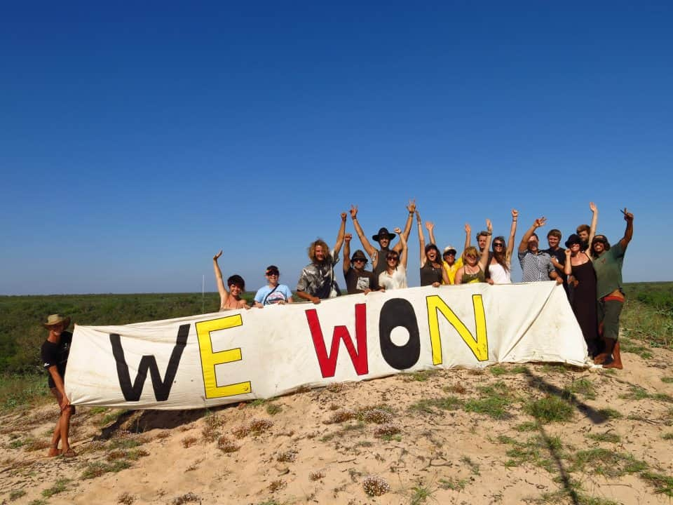 A jubilant group of people pose behind a large banner reading 'We won'. They are at the beach with sky and ocean in the background.