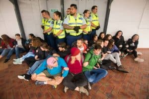 A group of police officers stand side by side, surrounded by seated activists with arms interlinked.