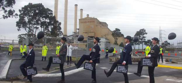 Photograph of people dressed in suits and bowler hats and brief cases walking together in front of a coal fired power station.