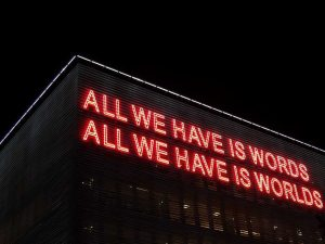 Photo of neon sign reading 'ALL WE HAVE ARE WORDS; ALL WE HAVE ARE WORLDS'