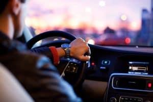Man driving car in traffic listening to radio
