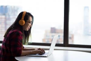 A woman sits at a laptop, wearing headphones. She sits in front of a window showing a city skyline.