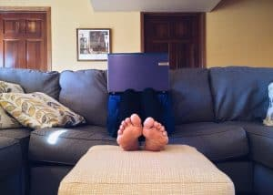 Photo of a person sitting on a couch holding a laptop.