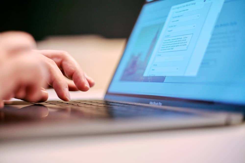 A close up of a person's hands typing on a laptop keyboard, with something indistinct on the screen.
