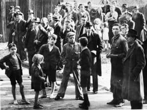 Black and white photo of a crowd of people including several children.