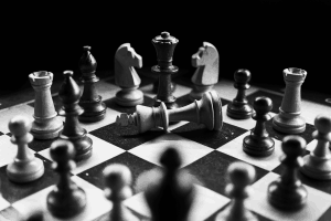 Black and white photograph of a chess board with overturned king..