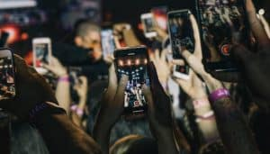 Shallow focus photograph of crowd taking live videos for social media