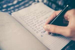 An open notebook in which a hand is writing a list of tasks, ready to be ticked off. The text is too indistinct to read.