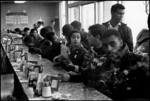 A number of African American students sit along a lunch counter.