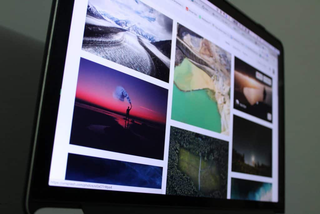 A computer screen displaying colourful, striking images, like a result of a google search. Most are out of focus, but in focus is a grand glacial valley, and a human figure silhouetted against the sunset, holding a bright flare.