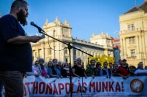 Máté speaks into a microphone at a protest outside the Hungarian Parliament. In the background protestors hold a large poster with Hungarian text.