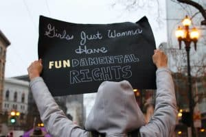 Photo of a woman at a rally taken from behind. She is wearing a grey hoodie sweatshirt and holding a sign that reads 'Girls just want to have FUNdamental rights'