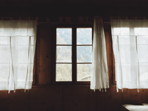Photograph of a window with curtains opening.