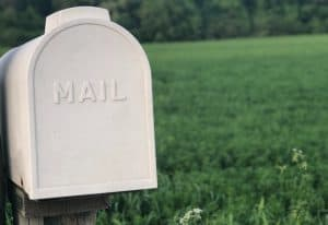 White mailbox sitting a field, with the word 'Mail' written on it.