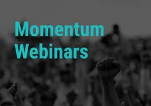A black and white photograph of a rally with people holding their fists in the air. The text 'Momentum Webinars' in written above it.