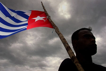 The Morning star flag, symbol of West Papuan independence, is flying against a grey cloudy sky. The person who is holding it is in silhouette.