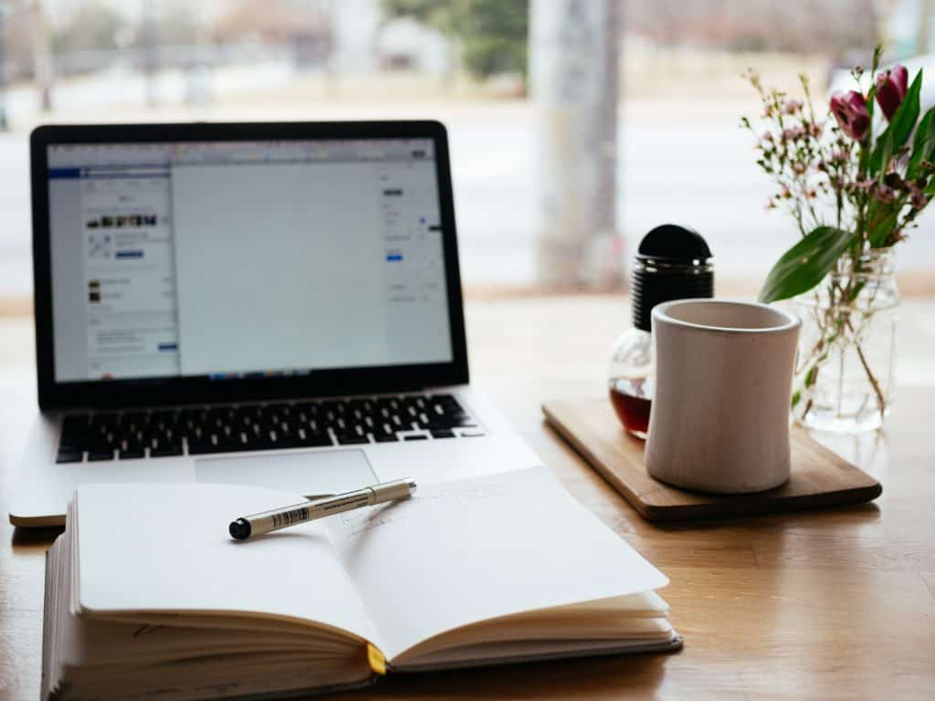A desk in a brightly lit room, with a laptop, coffee and coffee cup, and a notebook and pen sitting on it.