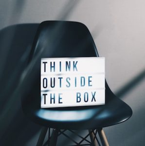A lit up light box sitting on a black chair saying: Think outside the box