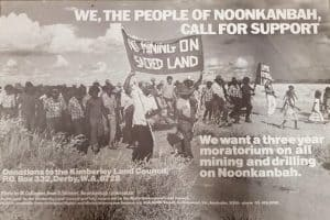 Protest poster - Aboriginal Australians in protest holding a sign that says No mining on sacred land. The wording on the poster says We, The People of Noonkanbah call for support.