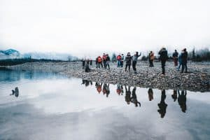 A small group of people stand on the beach of a beautiful lake, wearing winter clothing