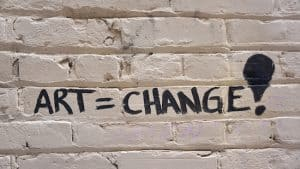 A brick wall painted white with the words Art = Change! graffitied in black