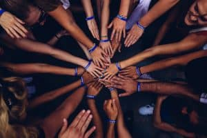 Over a dozen hands reach into the middle of a circle, making the 'all in' symbol