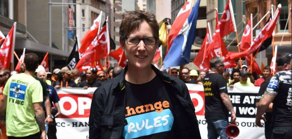 Sally McManus wears a 'Change the Rules' tshirt in front of a large crowd of workers holding banners and flags.