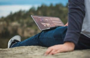 A person sitting outside on a rock, with a laptop on their lap