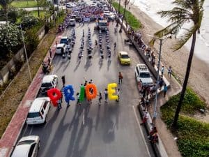 Group of people leading a march with the word pride spelled out using coloured balloons