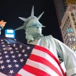 Photograph of someone dressed as the Statue of Liberty draped in the US flag.