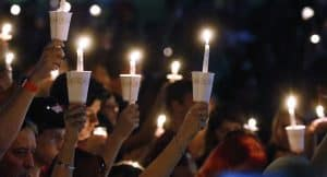 Photograph of hands holding cups with lit candles against the dark sky.