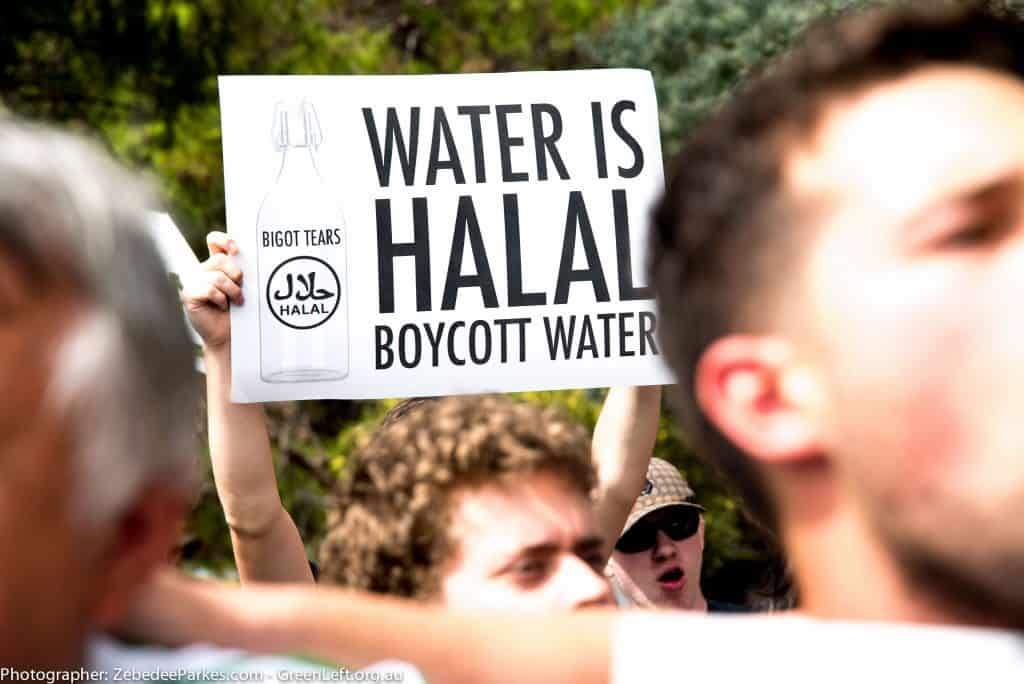 Close up of a placard being held above a crowd. It reads 'Water is Halal. Boycott Water.'