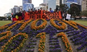Protestors holding banner that says CHOGM Protest Fri 28 October in front of flower display that spells out CHOGM 2011